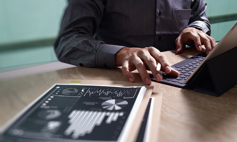 Man working on a tablet referencing a printed graph