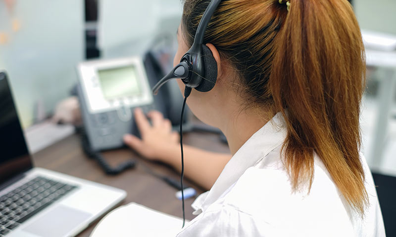 Young woman wearing a headset ansew