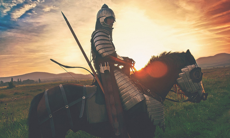 Photo of a knight sitting on on a horse in a field at sunset.