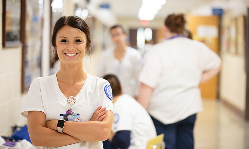 A nursing student in scrubs smiling with other students in the background