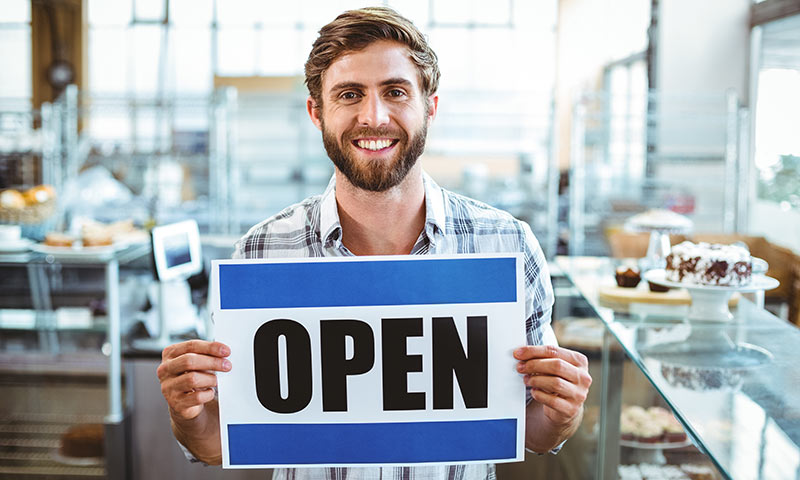 A young man holding an Open sign for a business