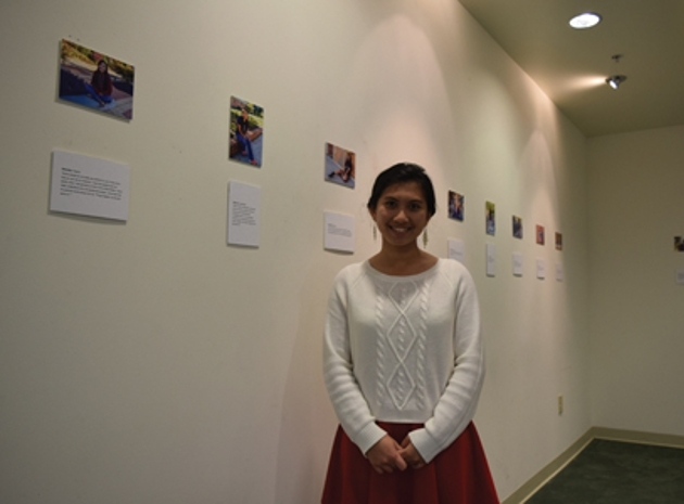 "Cleveland State Art student Bianca Dedicatoria completed her first solo art exhibition titled ""Cultural Diversity in America, 2016."" Pictured: Dedicatoria stands in front of her exhibition located in CSCC's George R. Johnson Cultural Heritage Center."